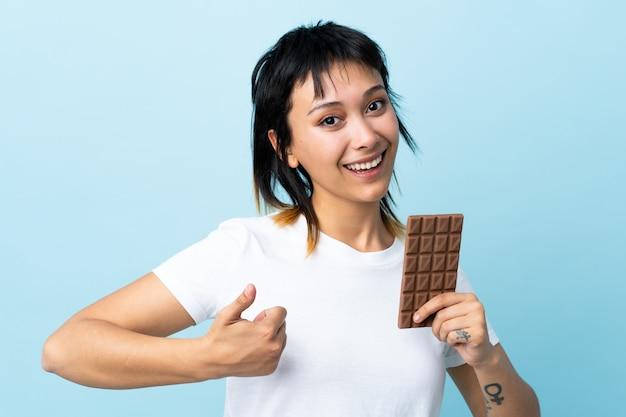 チョコレートタブレットを取ると親指で孤立した青以上の若い女性