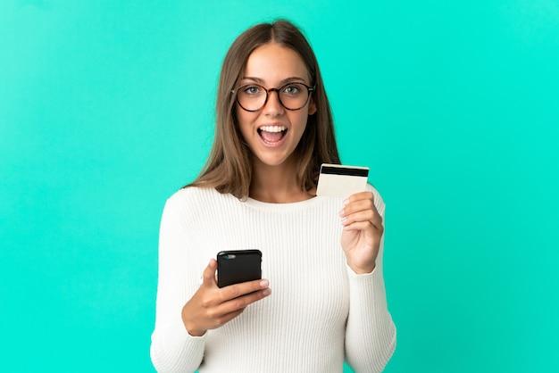 Молодая женщина над изолированной синей стеной покупает с помощью мобильного телефона и держит кредитную карту с удивленным выражением лица