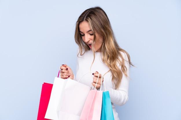 격리 된 파란색 벽 쇼핑백을 들고 그 안에 찾고 젊은 여자
