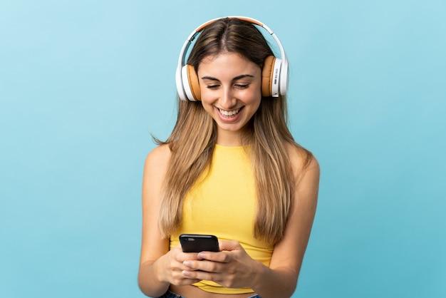 孤立した青い壁の上の若い女性が音楽を聴いて、モバイルを探しています