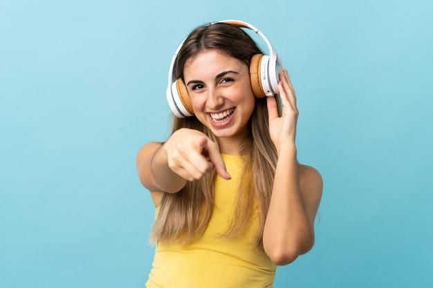 音楽を聴き、正面を指して青い壁に孤立した若い女性
