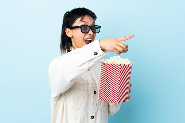 Молодая женщина над изолированной синей с 3d-очки и проведение большой ведро попкорна, указывая в сторону
