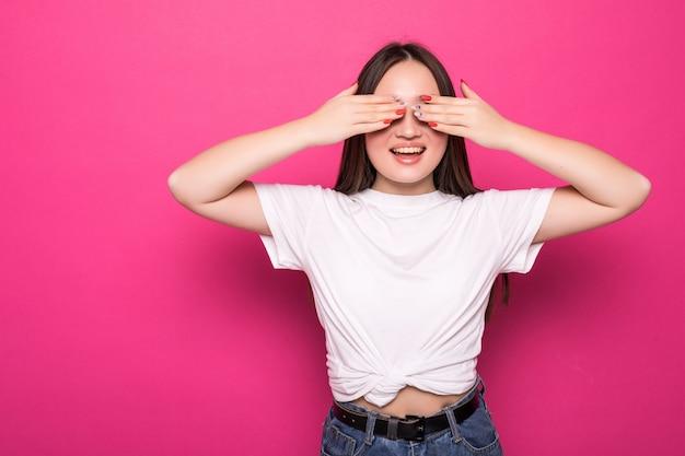 Молодая женщина за изолированные розовые стены покрытия глаза руками