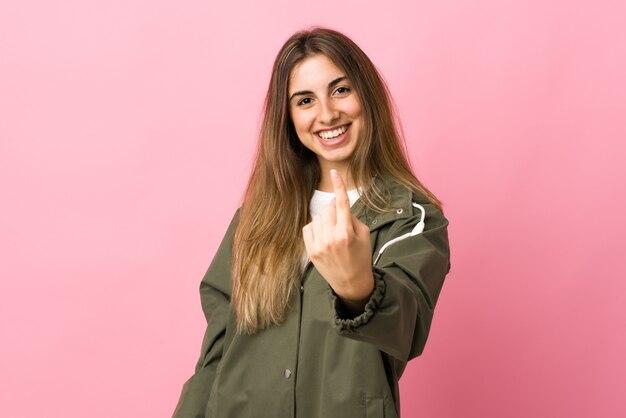 Молодая женщина над изолированной розовой стеной делает приближающийся жест