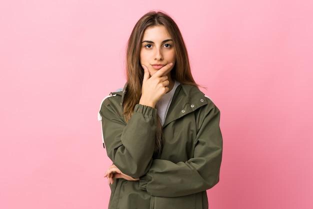 孤立したピンクの壁の思考以上の若い女性