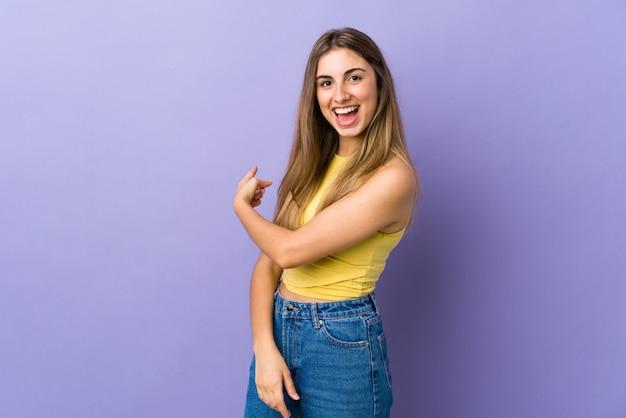 指している孤立した紫色の背景の上の若い女性