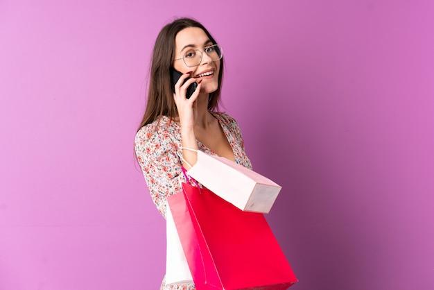 Молодая женщина над изолированной фиолетовой стеной держа хозяйственные сумки и вызывая друга с ее сотовым телефоном