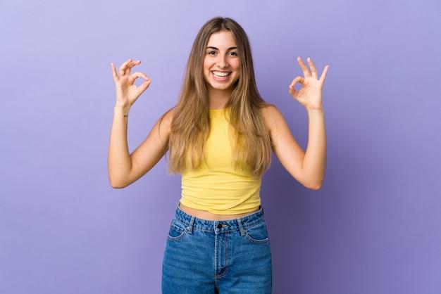 2つの手でokの標識を示す孤立した紫色の壁を越えて若い女性