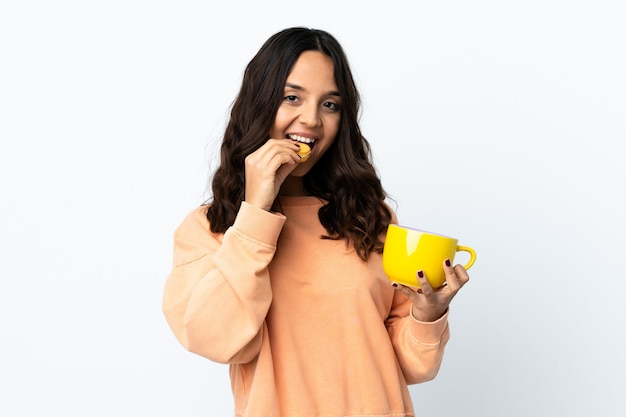 カラフルなフランスのマカロンとミルクのカップを保持している孤立した白い背景の上の若い女性