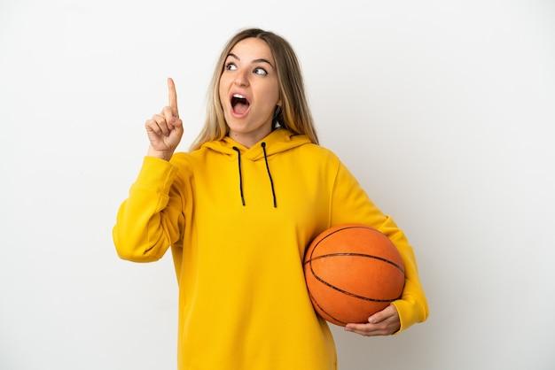 バスケットボールをしてアイデアを持っている孤立した白い背景の上の若い女性