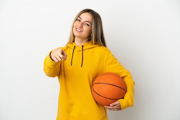 バスケットボールをし、正面を指して孤立した白い背景の上の若い女性