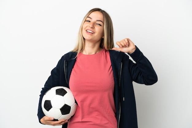 Молодая женщина на изолированном белом фоне с футбольным мячом и гордится собой
