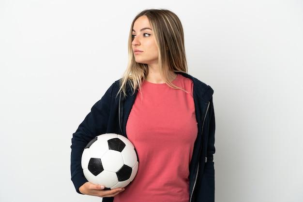 Молодая женщина на изолированном белом фоне с футбольным мячом