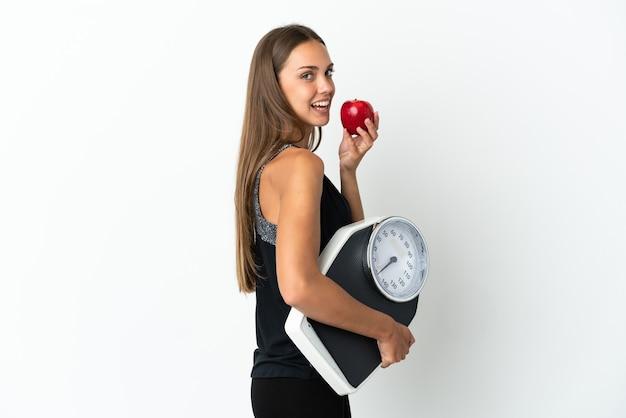기계 무게와 사과와 격리 된 흰색 배경 위에 젊은 여자
