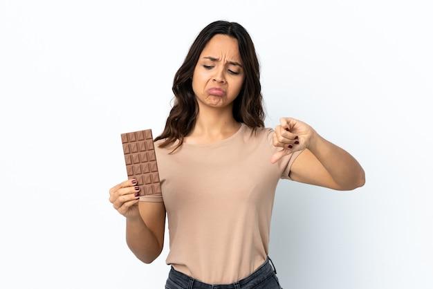 チョコレートの錠剤を服用している孤立した白の若い女性