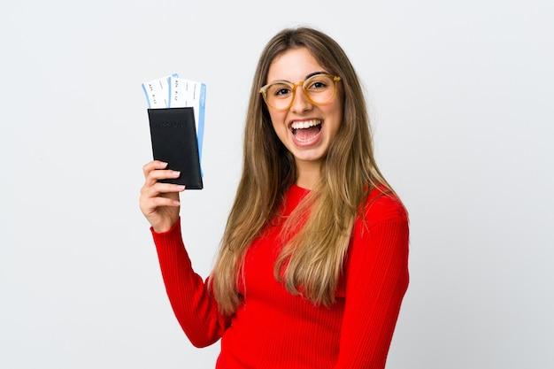 Молодая женщина над изолированной белой стеной счастлива в отпуске с паспортом и билетами на самолет