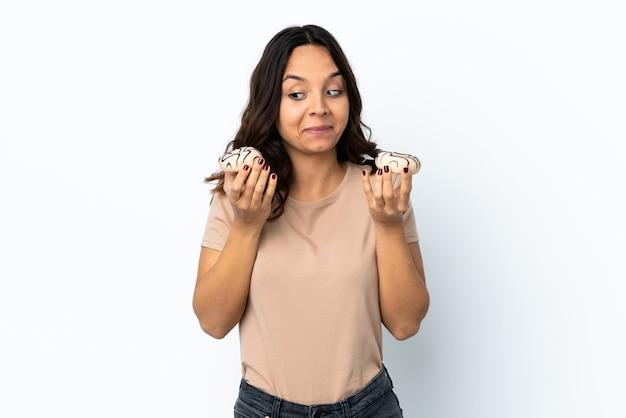 ドーナツを保持している孤立した白い壁の上の若い女性