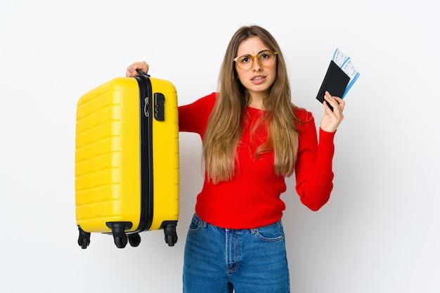 スーツケースとパスポートで休暇中に不幸な孤立した白い壁の上の若い女性