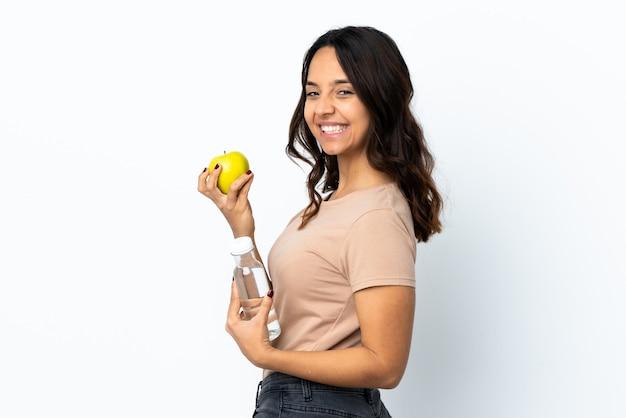 사과와 물 한 병 격리 된 흰 벽 위에 젊은 여자
