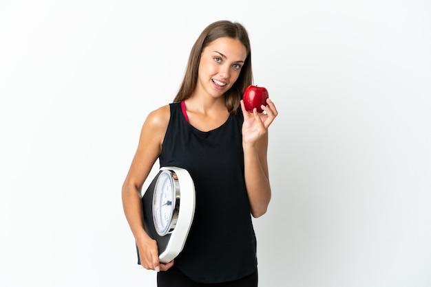 무게 기계와 사과와 격리 된 흰 벽 위에 젊은 여자