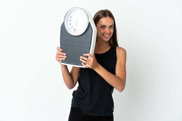기계 무게와 격리 된 흰 벽에 젊은 여자