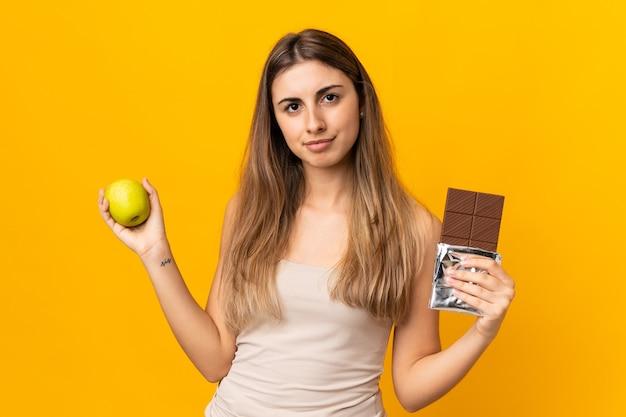 片手にチョコレートタブレット、もう片方の手にリンゴを取りながら疑問を持っている孤立した黄色の壁の上の若い女性