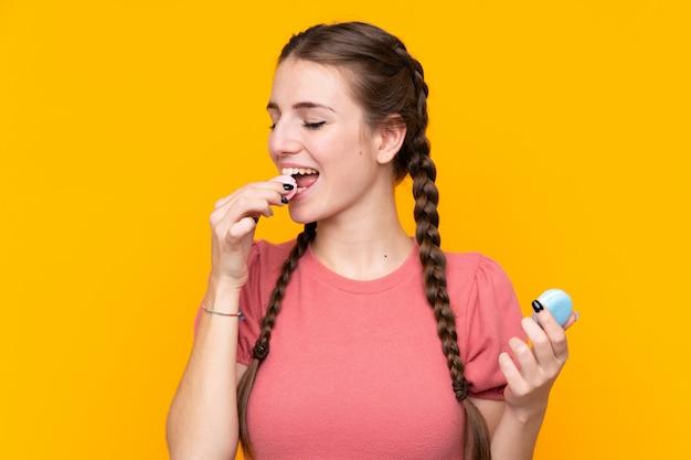 Молодая женщина над изолированной желтой стеной держа красочные французские macarons и есть его