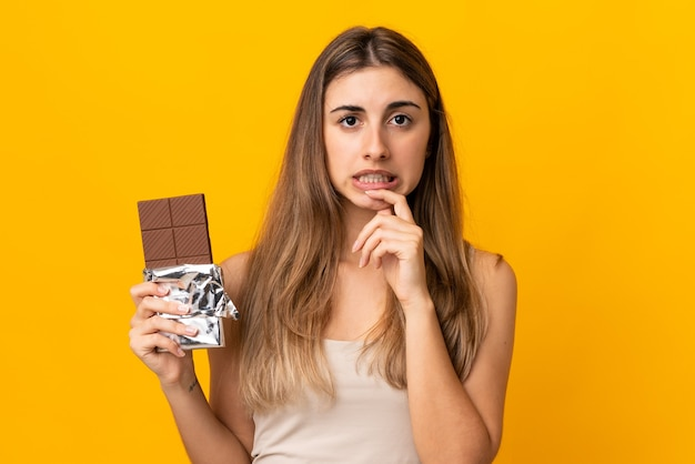 チョコレートのタブレットを取り、疑いを持っている孤立した黄色の壁の上の若い女性