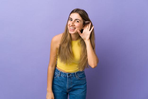 Молодая женщина над фиолетовой стеной слушает что-то, положив руку на ухо