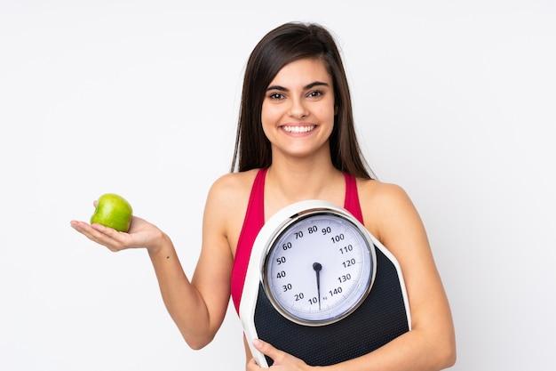 Молодая женщина над белой стеной с весами и яблоком