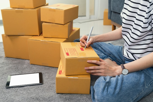 Young woman owner working and packing on box to customer at the sofa in home office, seller prepares the delivery.