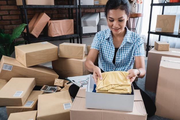 Молодая женщина упаковывает одежду, положенную на коробки