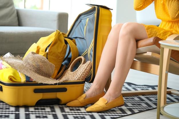 若い女性が自宅でスーツケースを荷造りします。旅行のコンセプト