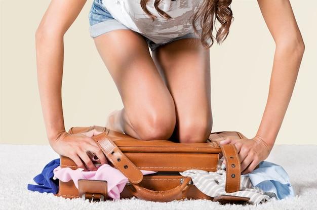背景にスーツケースを梱包する若い女性
