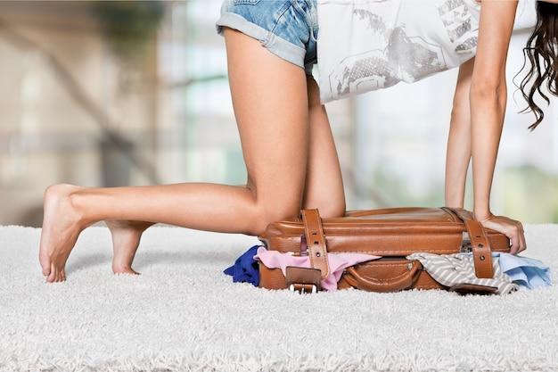 スーツケースを詰めて、それを閉じようとしている若い女性