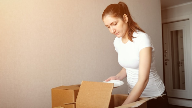 Young woman packs dishes in cardboard box, sunlight