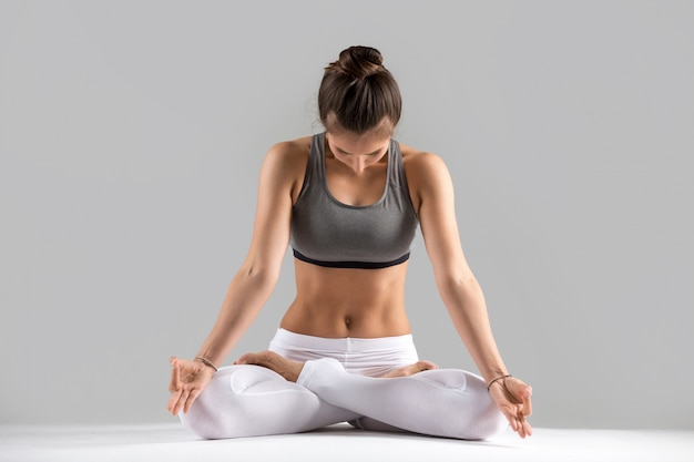 Young woman in padmasana pose, grey studio background