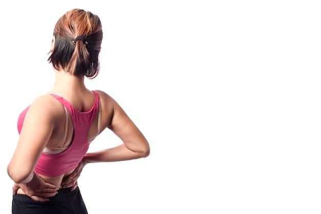 腰の若い女性の痛み、痛みのアクションで腰の筋肉領域に両手を持っている女性