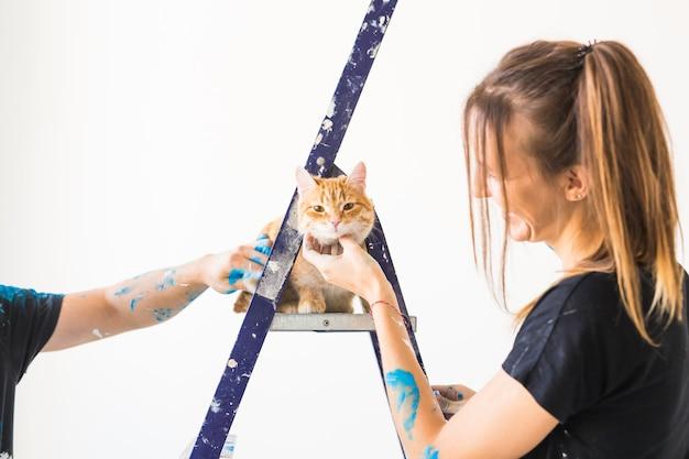 젊은 여자 화가 디자이너와 노동자는 고양이가 사다리에 앉아 벽에 페인트