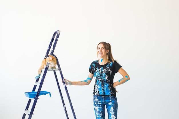 若い女性の画家、デザイナー、労働者が壁をペイントします。