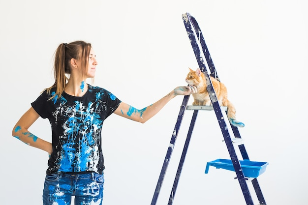 猫をなでる若い女性画家、デザイナー、労働者が壁をペイントします。