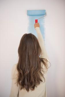 Молодая женщина рисует синюю стену
