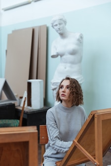 Young woman painting or drawing while sitting
