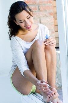 若い女性が彼女の釘を家に描く