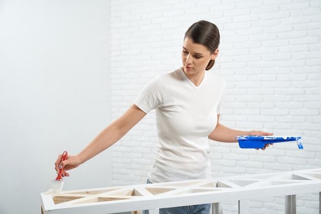 Young woman painting rack in white color