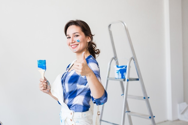 Young woman painting the wall and looks like very happy, she showing thumb up
