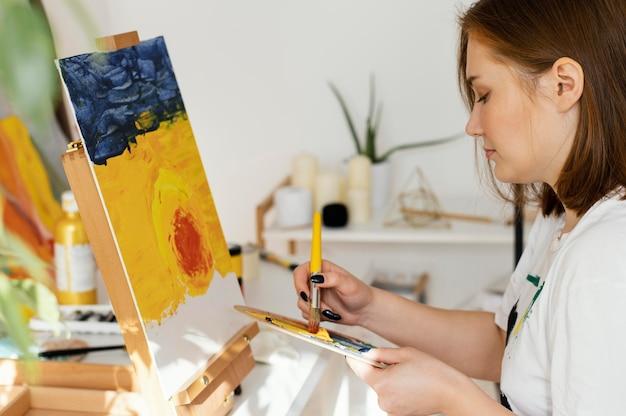 自宅でアクリル絵の具で絵を描く若い女性