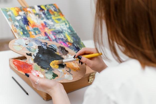 アクリル絵の具で絵を描く若い女性