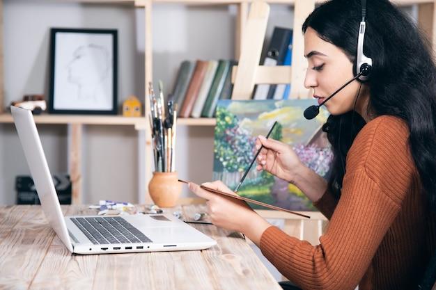 Молодая женщина рисует с онлайн-образованием