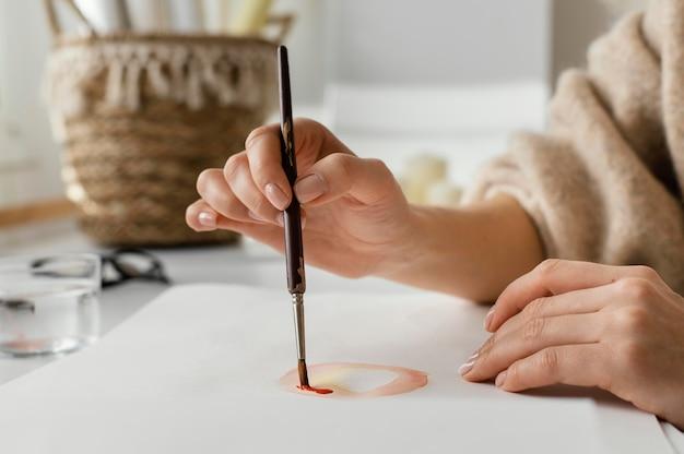 Молодая женщина рисует акварелью на бумаге